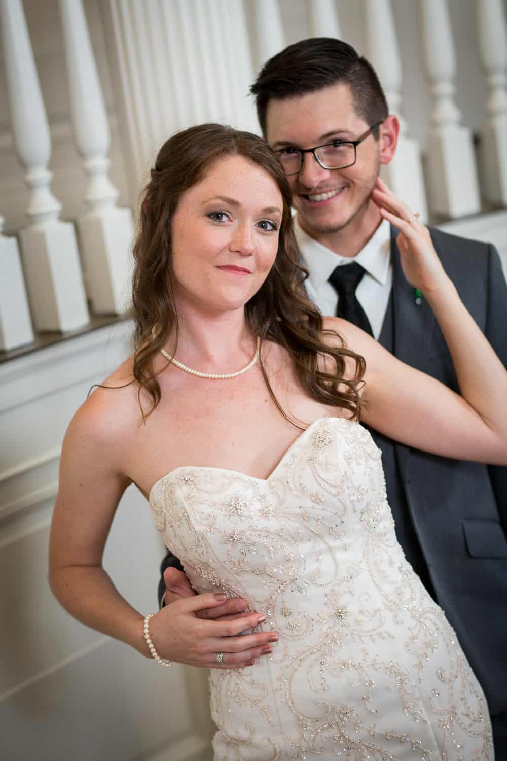 bride with her back on her groom's chest and her arm up embracing his face.