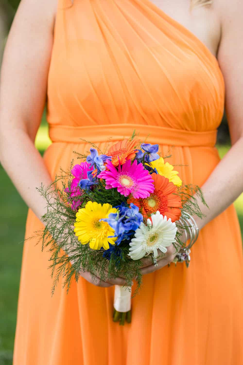 Summer flowers and bright orange dresses for a wedding.