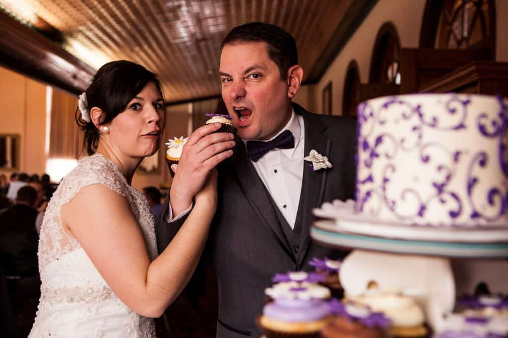 Lori and Bryan eat cake at their wedding at the German House in Rochester.