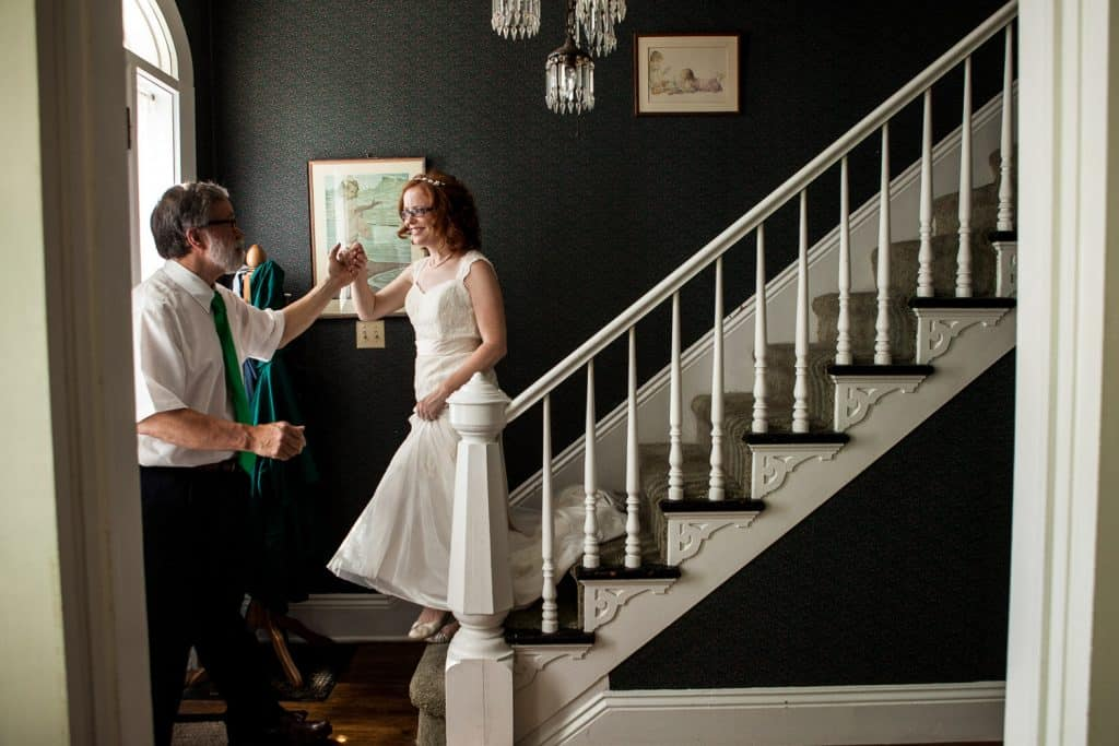 A bride walks down stairs and sees her father during their first look.