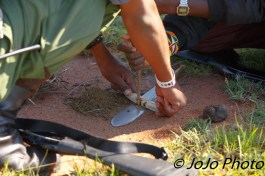 Maasai warriors use dried zebra dung, machete, and sticks for fire building.