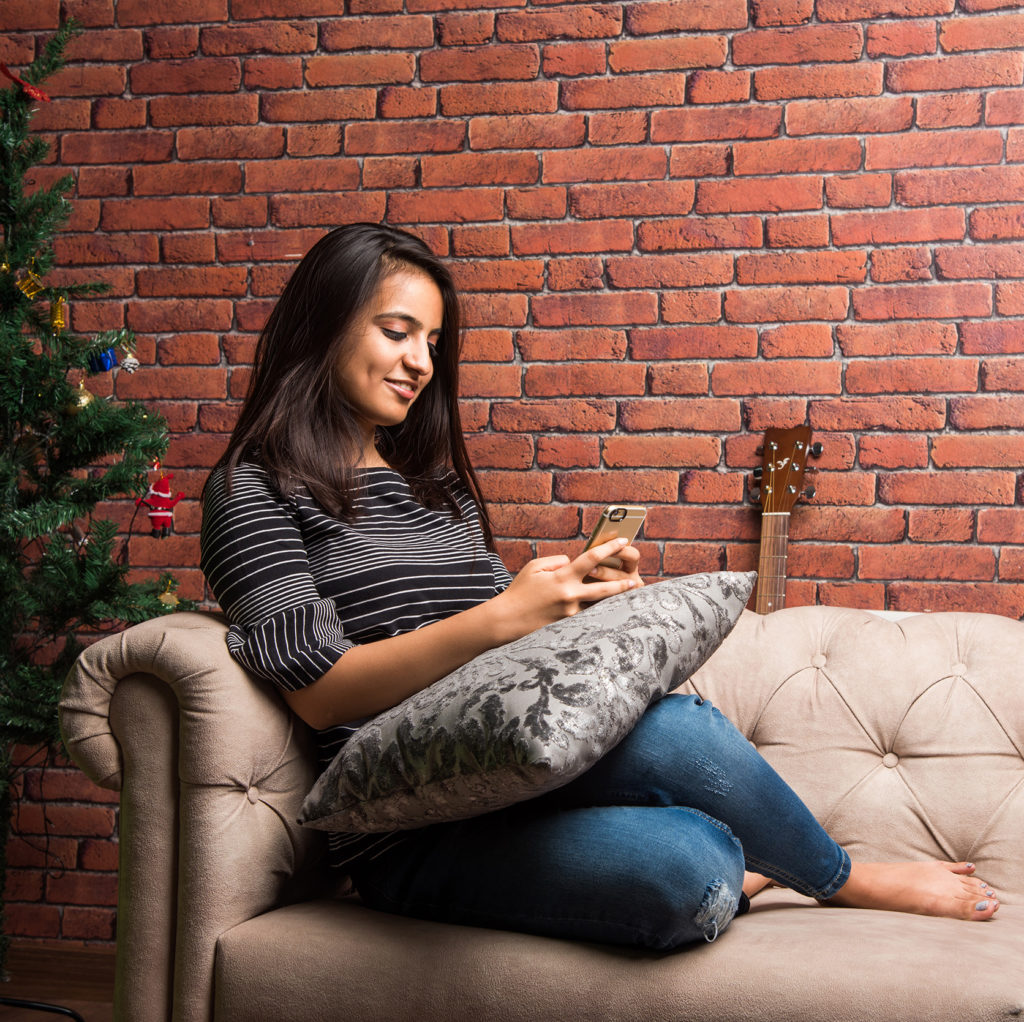 woman texting on a couch
