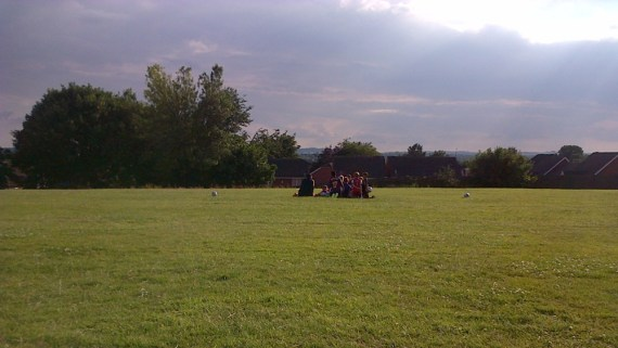 Boys and a football manager on a green field on a summer's day
