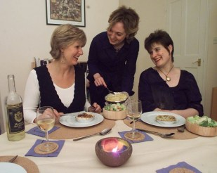 Two ladies seated with food on their plates and a third, between them, serving them. For Jo Ind's blog - What is a writer?