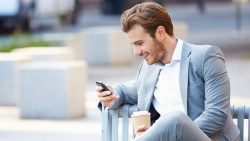 Man outside smiling with phone