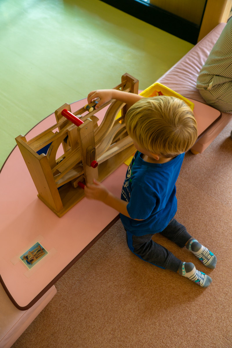 Kodomokan boy playing with wooden car track