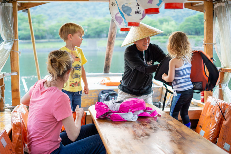 Ukai boatman helping with girls life jacket