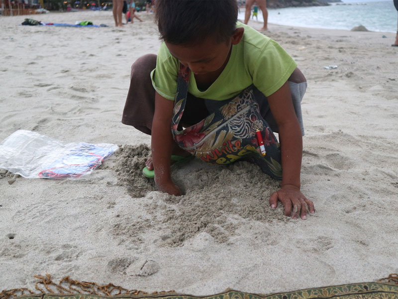 a kid digging in the sand