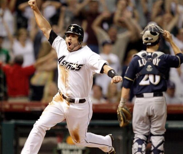 Steve Pearce celebrates scoring a run for the Houston Astros as Milwaukee Brewers catcher Jonathan Lucroy looks on, pulling off his mask