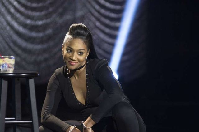 Tiffany Haddish bends down and gazes into the crowd with a smirk on her face during her Showtime Comedy Special.