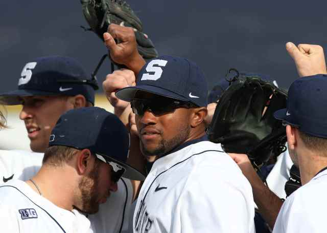 Coach Andre Butler breaks down the huddle with his outfielders