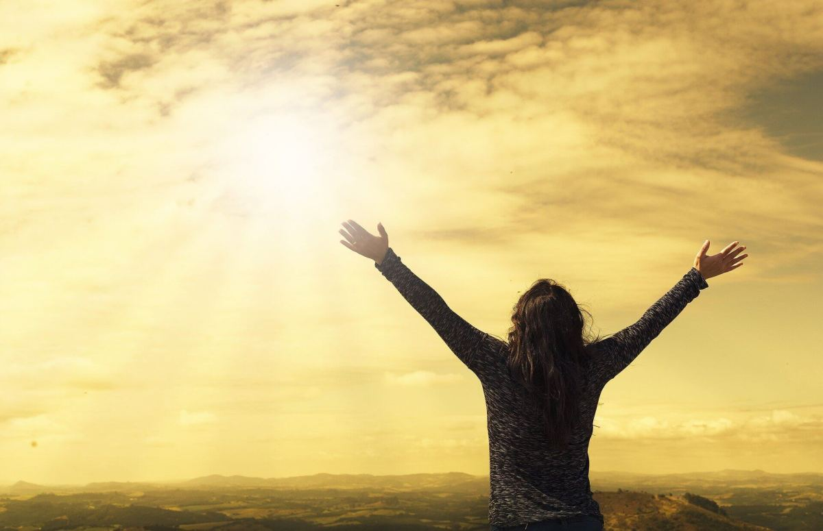 An image of a woman with her hands in the air and looking towards the sky