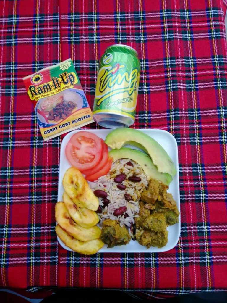 A plate of Jamaican curried goat with a can of Ting soda