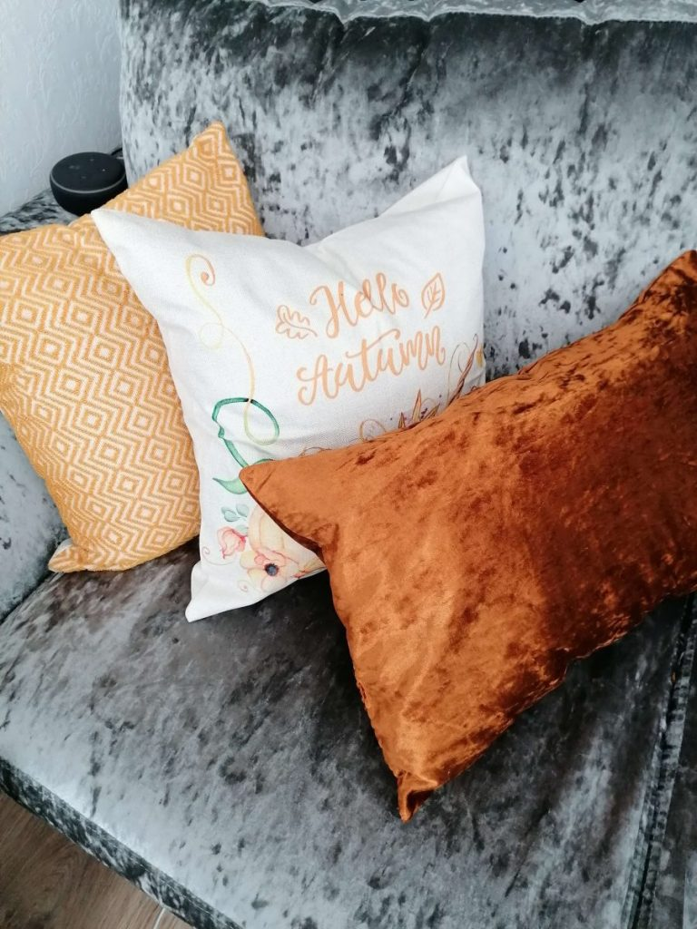 three cushions on a sofa for decorating for fall on a budget