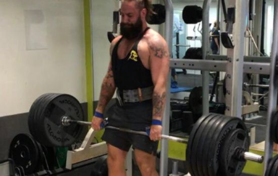 man lifting heavy weights in a gym