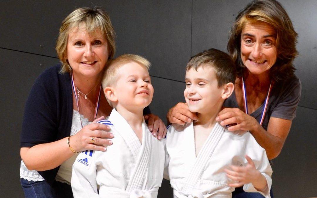 Deux enfants qui font du judo avec des encadrants