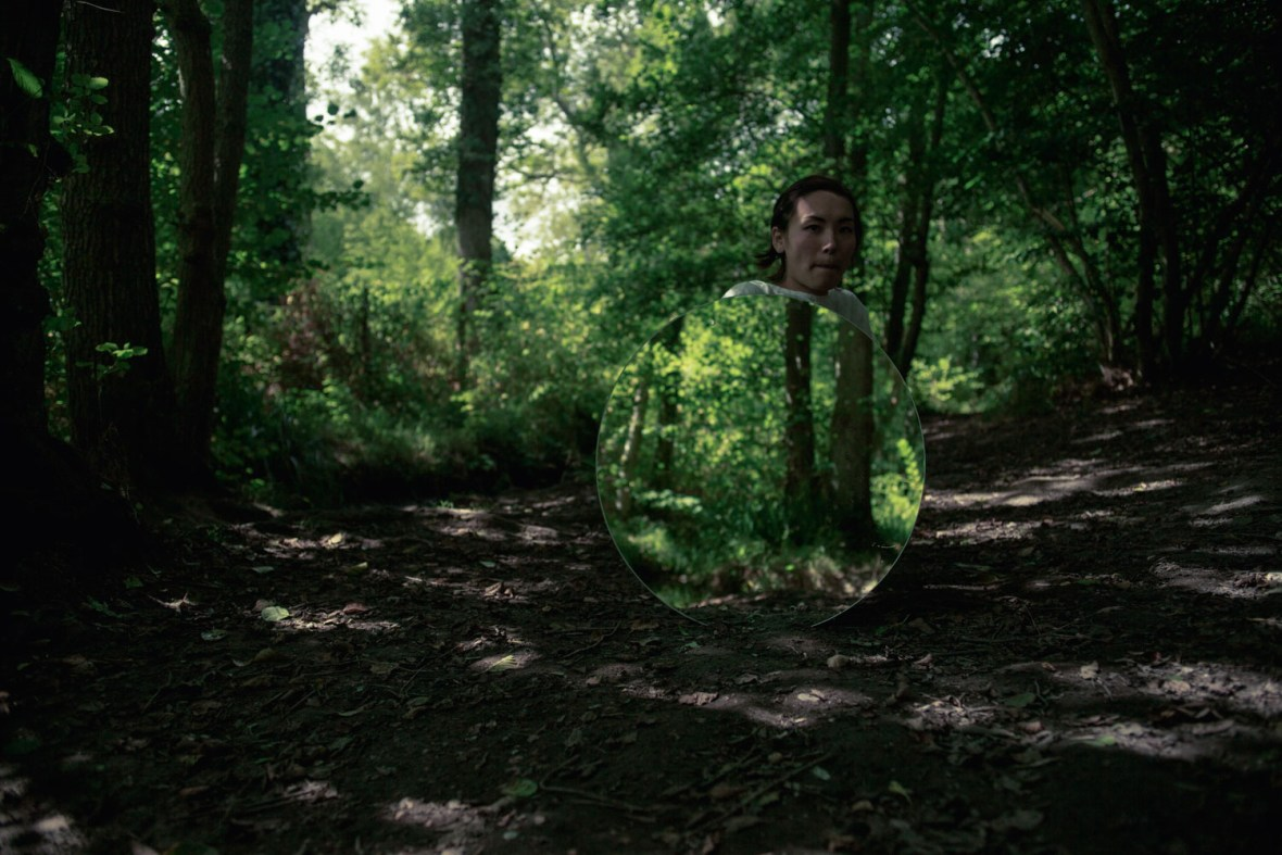 A video still of a woman crouched behind a mirror in a forrest.