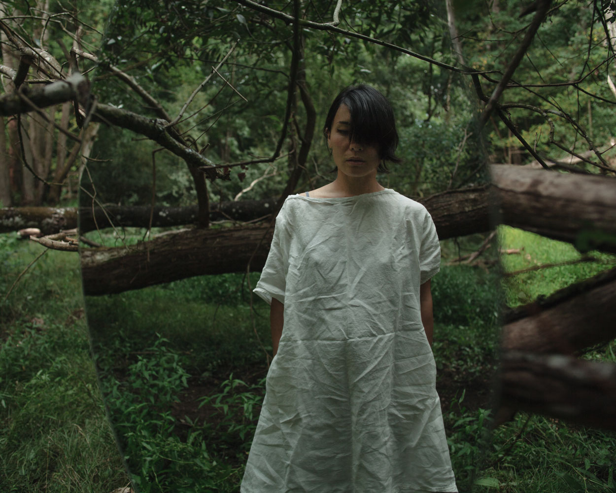 Photograph of a woman reflecting in a mirror in a forest.