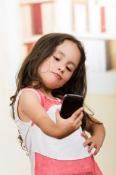 http://www.dreamstime.com/royalty-free-stock-image-cute-little-girl-using-cell-phone-taking-selfie-portrait-happy-image52775476