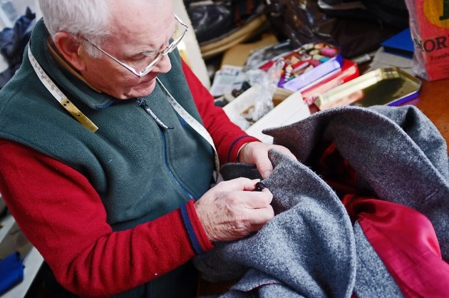 Mel Woodhead sewing a button onto a double brested Harris Tweed overcoat/jacket.