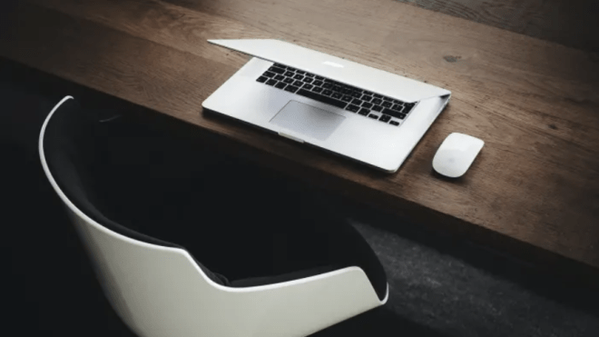 macbook and mouse on a table next to a white chair