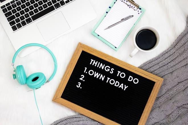 A chalkboard on a bed next to a laptop, headphones and a notepad. Chalkboard says, Things to Do - 1, Own today.