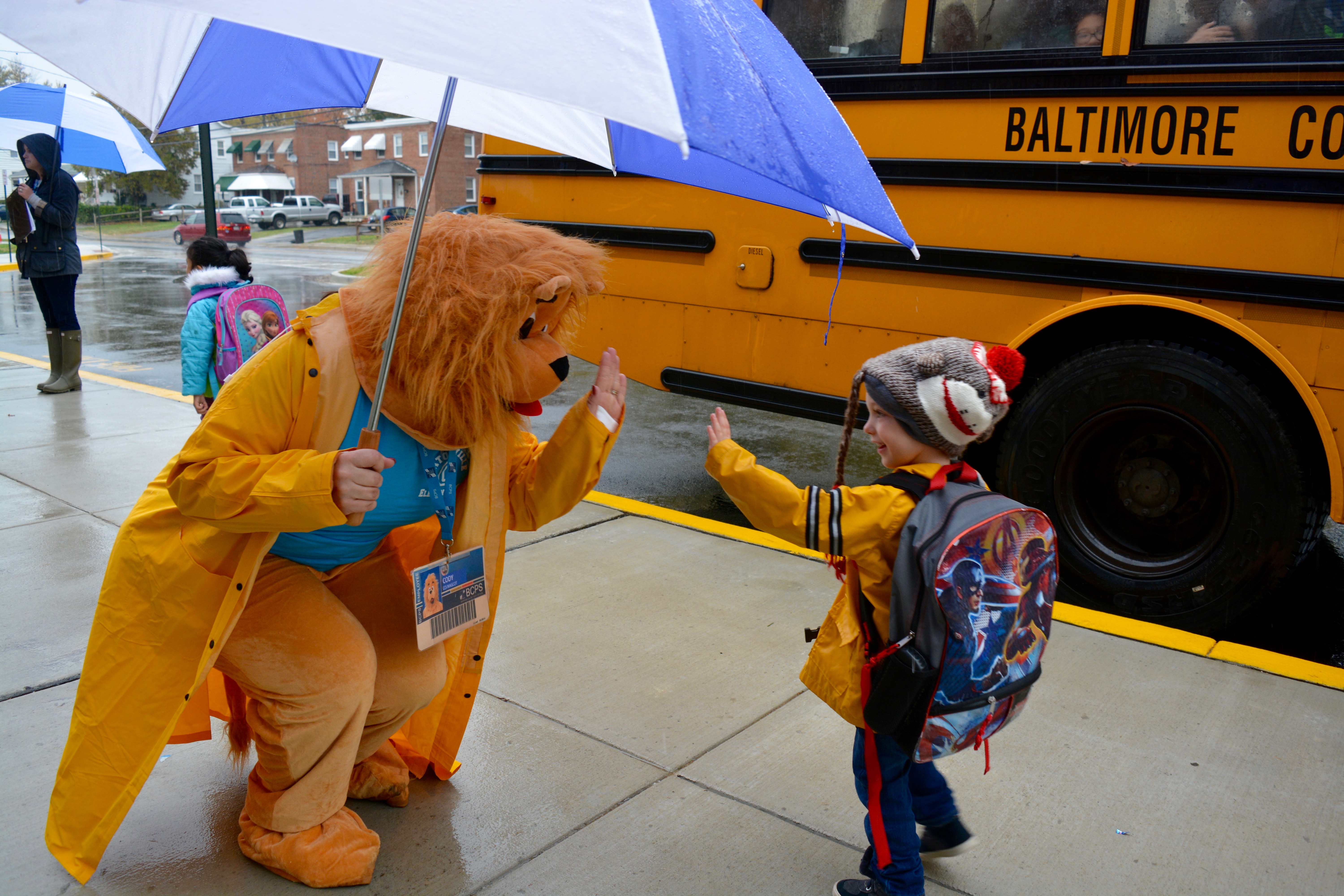 Cody the Cub, the newly named mascot of Catonsville Elementary School, greets students as they enter the school Wednesday, Nov. 9.
