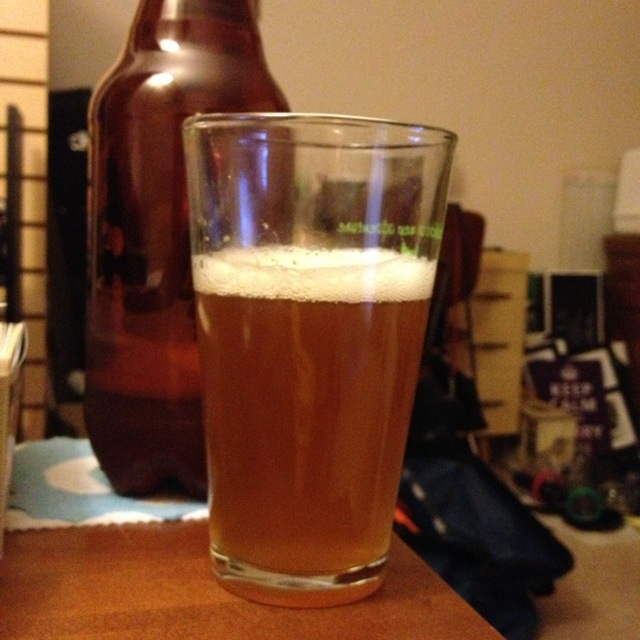 A glass of home brewed west coast pale ale next to a bottle
