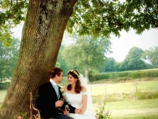 Bride and Groom sitting under an oak tree