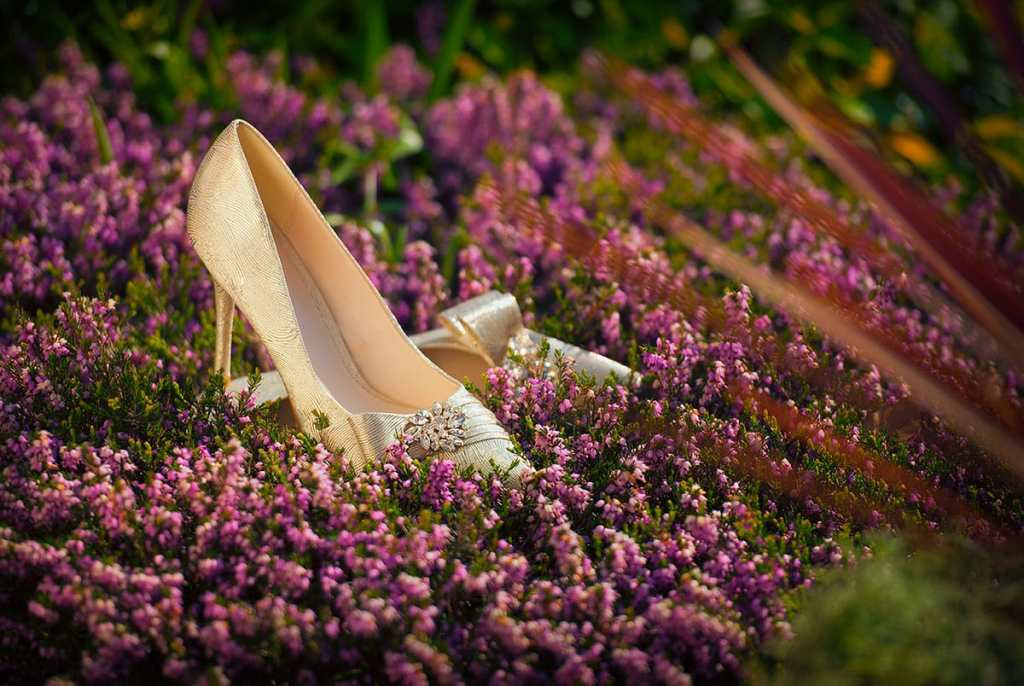 Silver wedding shoes on heather in bloom