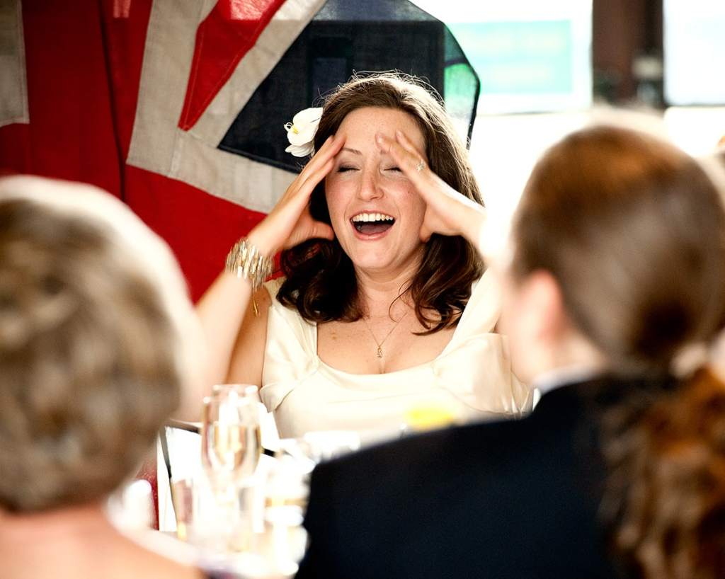 Bride holding her head laughing at the wedding speeches