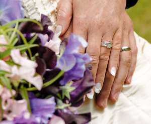 Hands of the bride and groom showing the rings and boquet