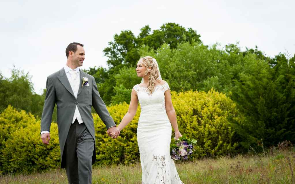 Bride and groom walking through a meadow