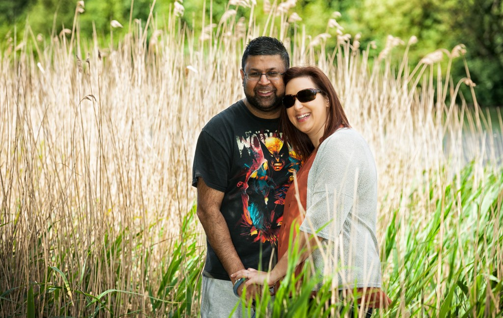 Couple holding hands with a pond and reeds in the background