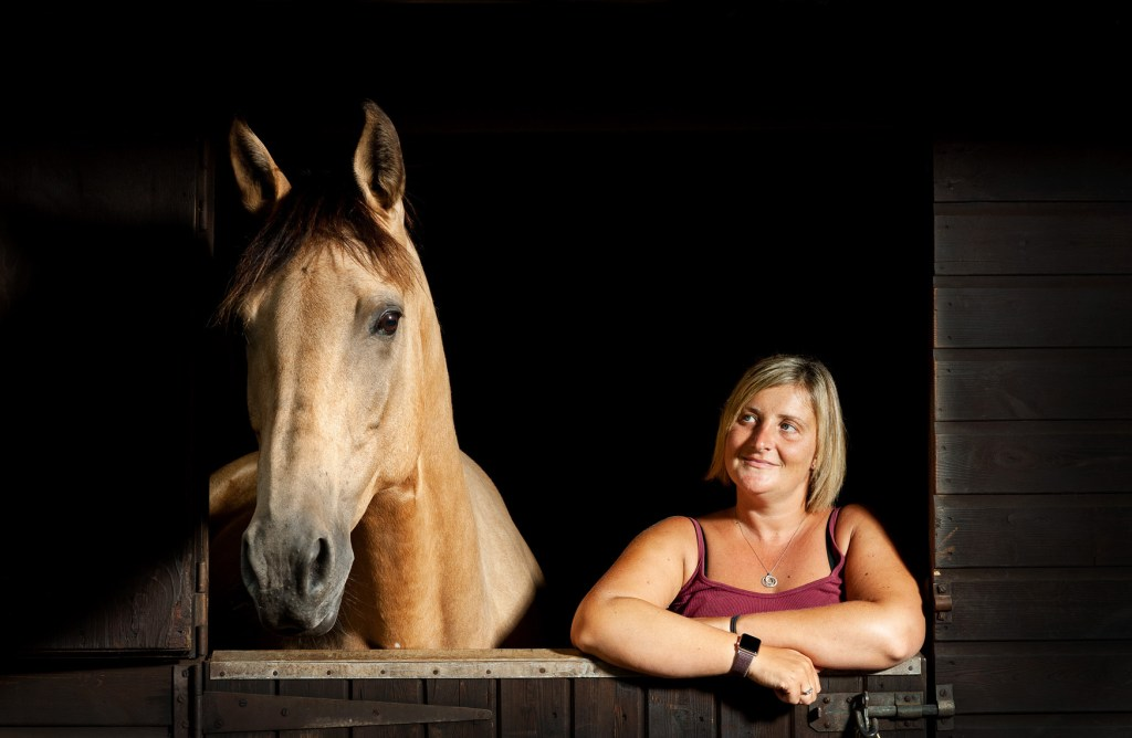 Horse and owner leaning over a stable door