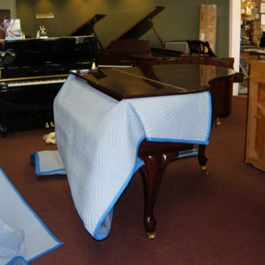 We protect the lid from banging against the piano with furniture pads.
