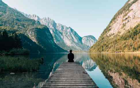 Man siting on gray dock inspiration valley mountains
