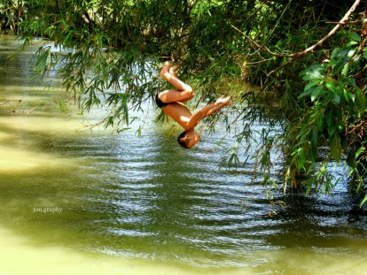 A kid somersaulted into the brown river.