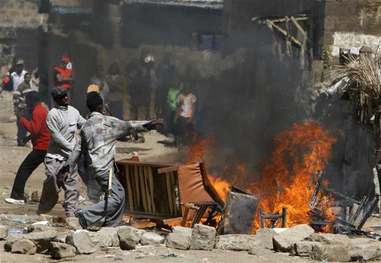 Kikuyu tribe members burn properties belonging to the Luo tribe during ethnic clashes in Naivasha town