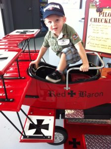 boy climbs into red baron model