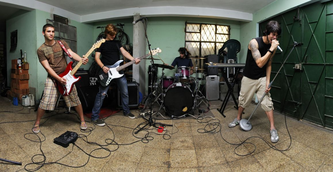 4343684 - group of young male musicians playing on messy garage