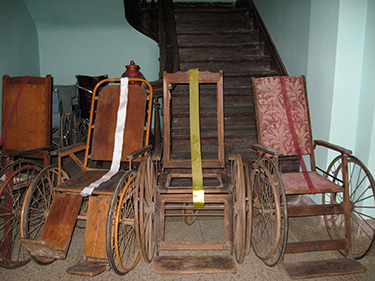 A collection of antique wheelchairs.