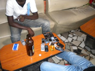 "6.- Second-hand mobile phone vendors taking a break over a ""drogba"" beer."