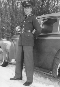 A photo of Mike Raddick, Sr. in front of a car wearing a U.S. Army uniform