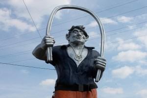A statue of Joe Magarac bending a steel beam