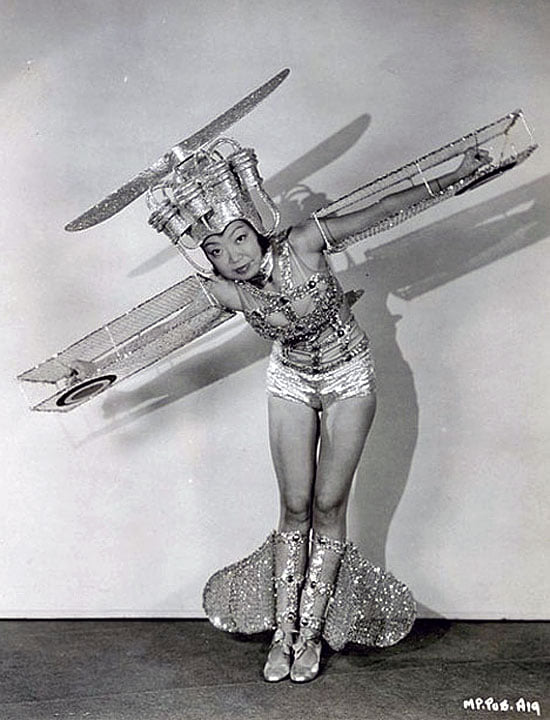 Vintage black-and-white photo: an Asian woman with short shorts, wings on her arms, and a propeller on her head
