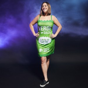 """A woman in a tight green dress labeled """"verde salsa"""""""