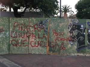 "Graffiti spray-painted in red on a wall: ""Piñera chupala que cuelga"""