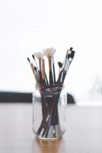 Assorted paint brushes in mason jar on desk against white background. Laura Jordan at Jordan Therapy Services has created courses! Now available for perinatal mental health and compassion in health is learn at home courses. Get lifetime access and a leg up in the medical field. Register today!