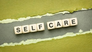 Self care written on blocks and torn green and black blocks. If you're ready to begin feeling some peace, consider my self-care for women course. You can learn at home about mental health basics on perinatal mental health. This online course gives you the building blocks to take on your postpartum anxiety and recover from new parent guilt.